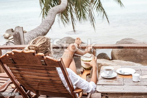 538041934 istock photo Young woman enjoys drinking coffee and coconut 538041746