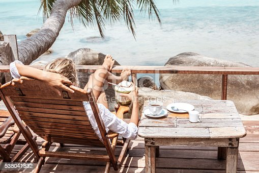 538041934 istock photo Young woman enjoys drinking coffee and coconut 538041832