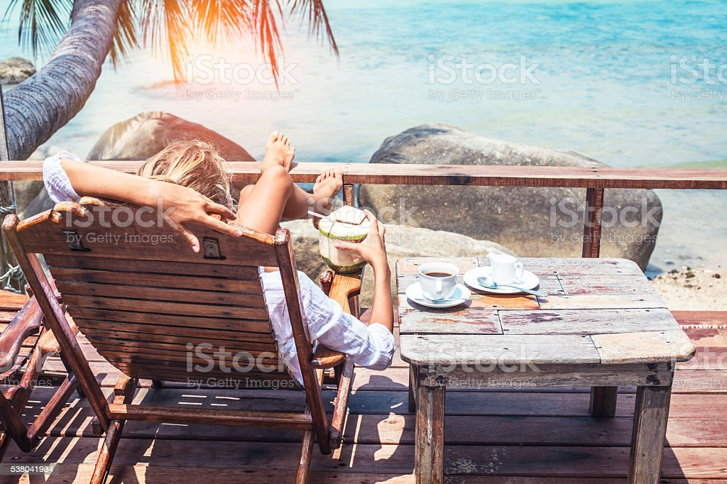 Young woman enjoys drinking coffee and coconut