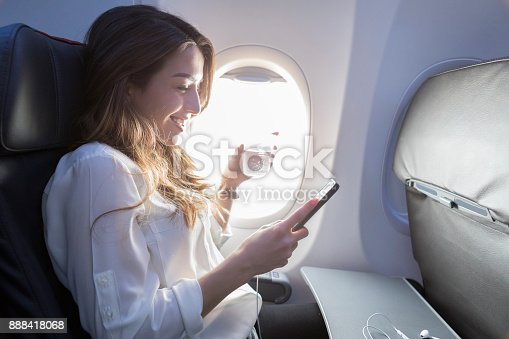 A smiling young woman sits in the window seat of her aircraft.  She holds a beverage in one hand and her smart phone in another as she enjoys the wifi.  Her earbuds rest on a tray in front of her.