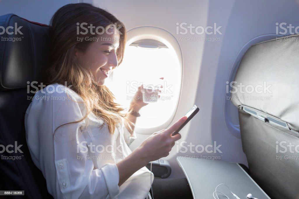 Young woman enjoys in flight beverage and wifi stock photo