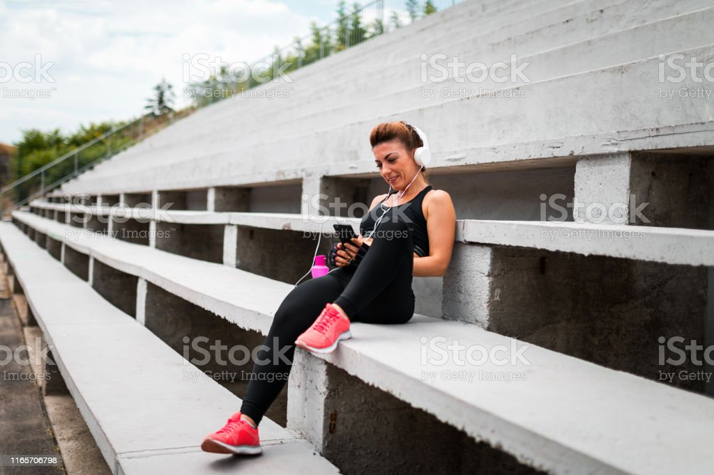 Young woman enjoys in music after exercise