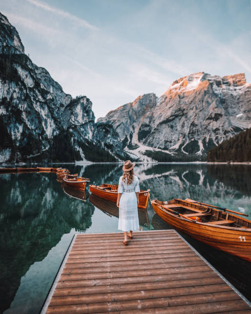 Young woman enjoys in nature on the coast of Braies Lake, Dolomites, Italy stock photo
