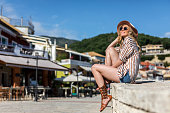 istock Young woman enjoys in the old city by the sea on vacation 1163533450