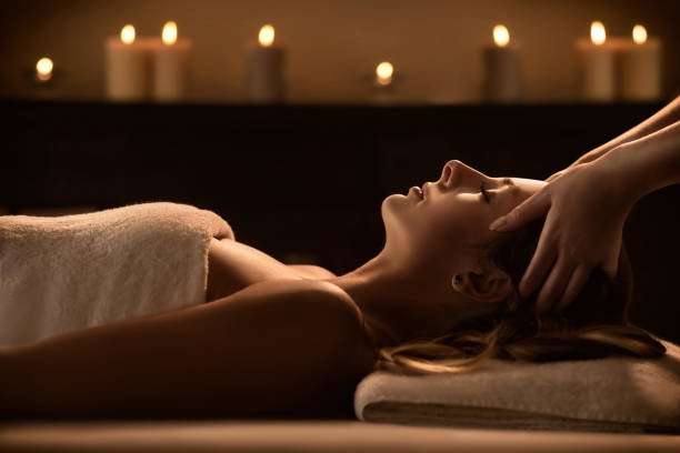 young woman enjoys massage in a luxury spa resort - massaggio foto e immagini stock