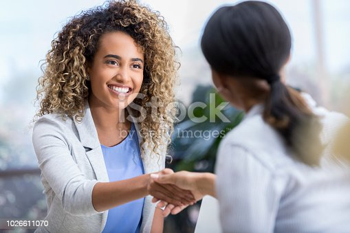 A beautiful young woman smiles and shakes hands with her new unrecognizable therapist.