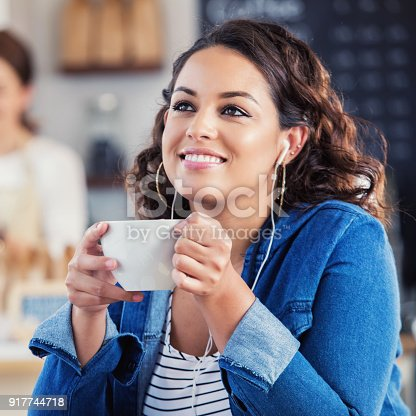 A smiling young woman sits at a table in a coffee shop. She daydreams as she listens to music on her earbuds and holds a mug of hot coffee.