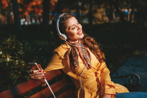 Junge Frau genießt Musik über die Kopfhörer im park – Foto