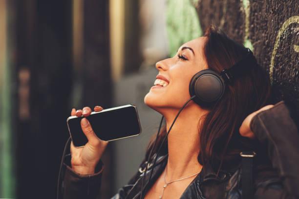 Young woman enjoys music via headphones on the street stock photo