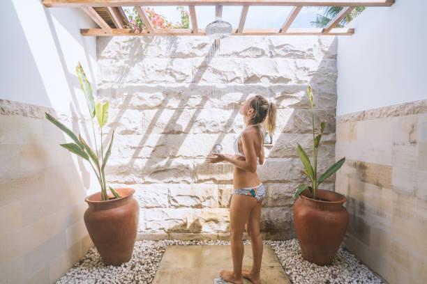 junge frau genießt outdoor regendusche in tropischem klima - sonnendusche stock-fotos und bilder