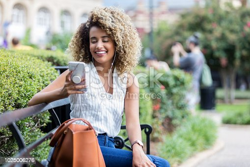 A cheerful young woman sits on a public park bench next to her large leather bag.  She looks down at her smart phone as she listens to music on her earbuds.