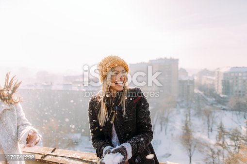 Young smiling woman enjoys snowy winter day on a rooftop terrace that overlooks the city