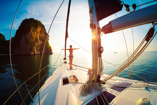 Young woman enjoys sunrise on the yacht anchored in the tropical sea stock photo