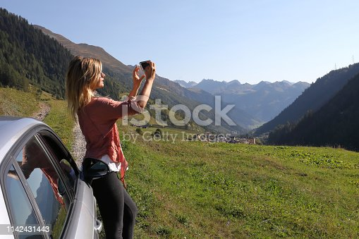 527894422 istock photo Young woman enjoys the view from her car 1142431443