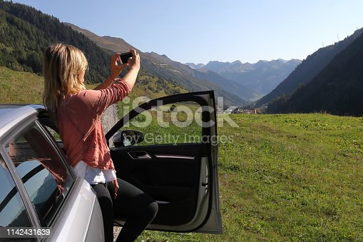 527894422 istock photo Young woman enjoys the view from her car 1142431639