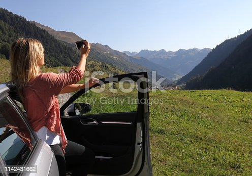 527894422 istock photo Young woman enjoys the view from her car 1142431662