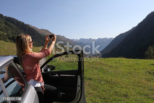 527894422 istock photo Young woman enjoys the view from her car 1142431736