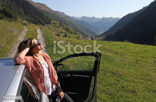 527894422 istock photo Young woman enjoys the view from her car 1142432603
