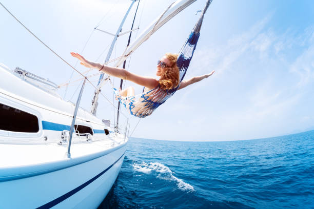 Young woman enjoys tropical sailing in the hammock set on the yacht stock photo