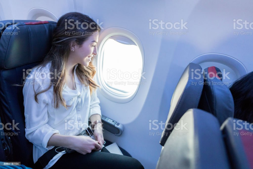 Young woman enjoys view from aircraft window seat stock photo