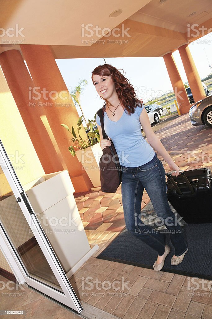 Young Woman Entering Hotel With Luggage royalty-free stock photo