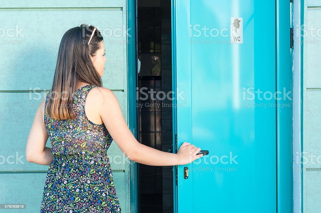 Young woman entering public toilet outside in park stock photo
