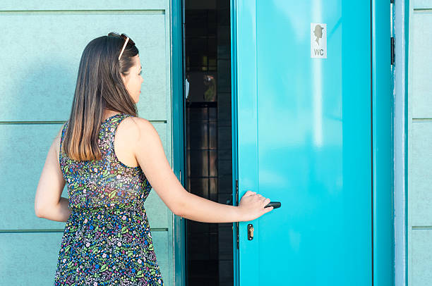 Young woman entering public toilet outside in park – Foto