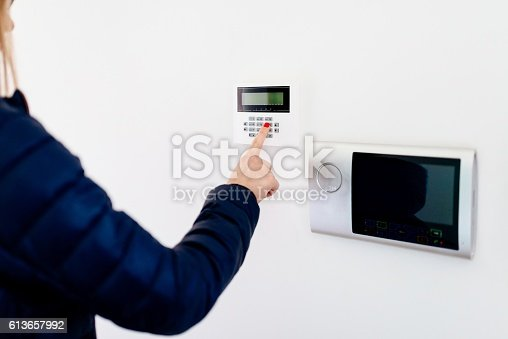 istock Young woman entering security code on keypad 613657992