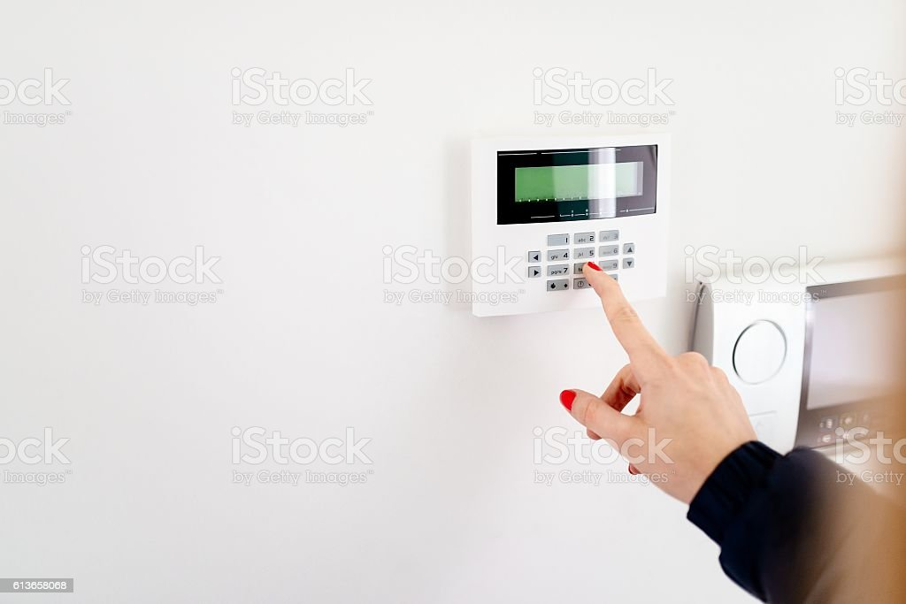 Young woman entering security code on keypad​​​ foto