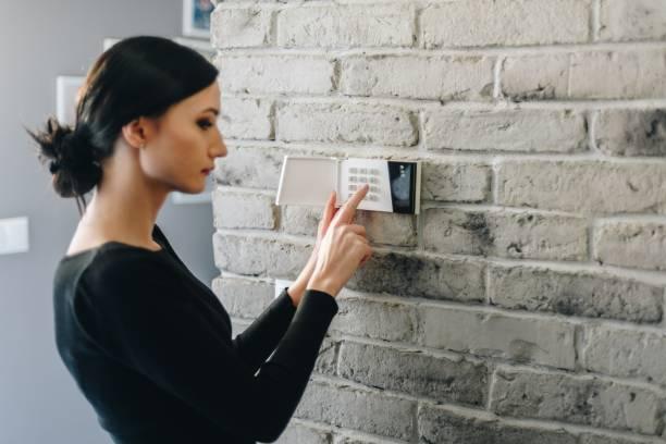 jonge vrouw invoeren veiligheid pin op huis alarm toetsenblok. - alarm, home, stockfoto's en -beelden