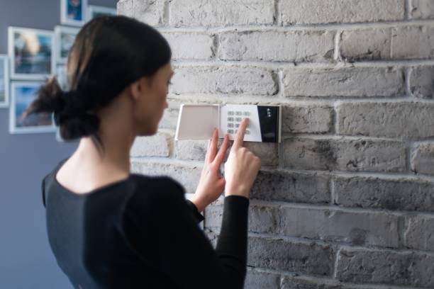 Young woman entering security pin on home alarm keypad. stock photo