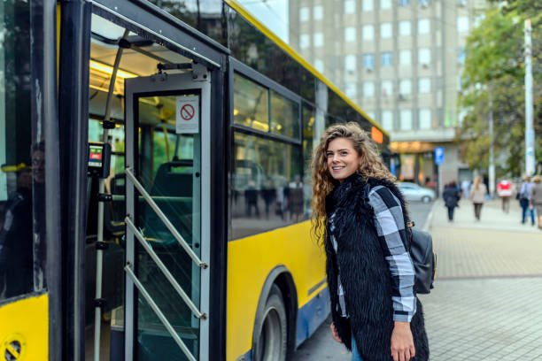 young woman enters bus - getting on stock photos and pictures
