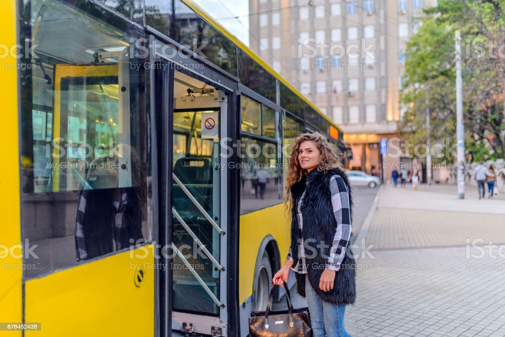 Young woman enters bus stock photo