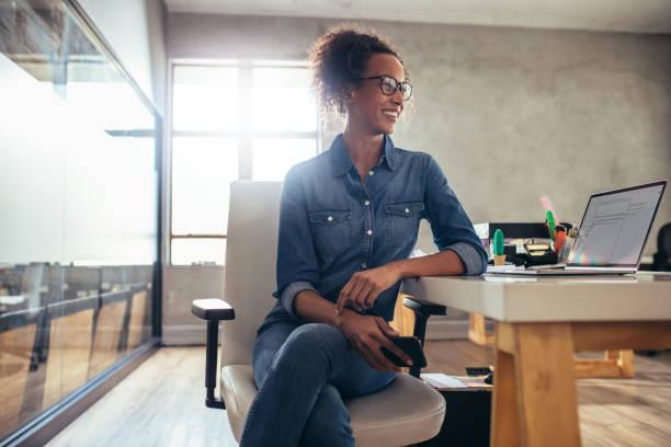 在她的書桌上的年輕女企業家 - 小型辦公室 個照片及圖片檔
