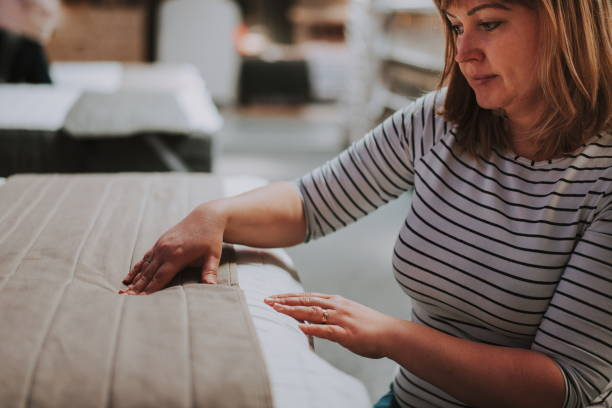 Young woman examining orthopaedic mattress in the shop. customer buying new bed and mattress Young woman choosing the right furniture for her apartment in a modern home furnishings store vivid filter. Woman hand pressing on white mattress. Side view. stock photo