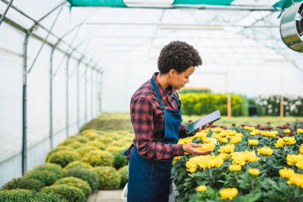 Junge Frau die Blumen zu prüfen und verwenden ein digitale tablet – Foto