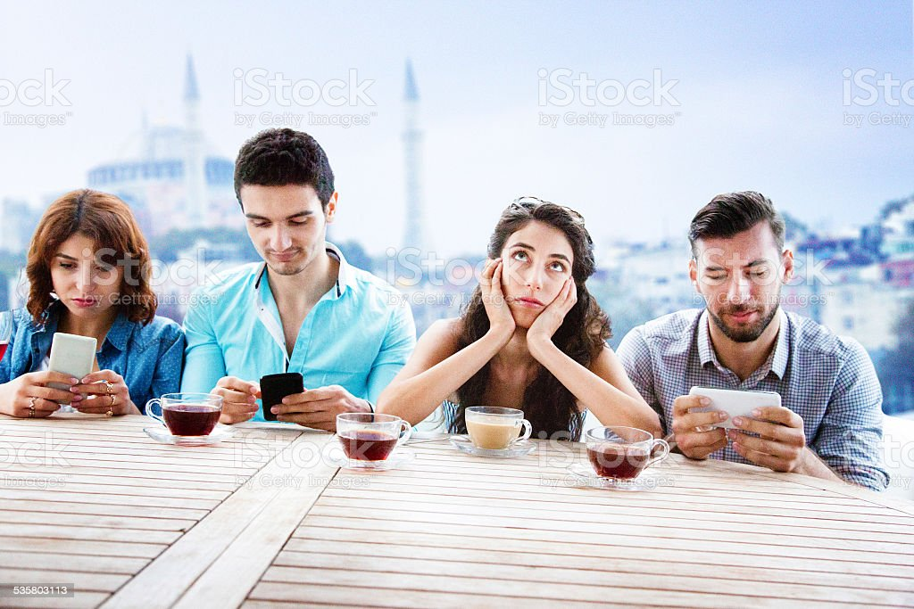 Young woman exasperated by her friends mobile phone obsession stock photo