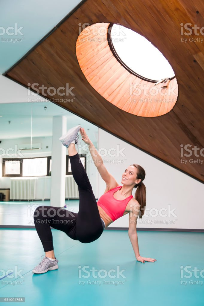 Young woman exercise in fitness studio on the floor royalty-free stock photo