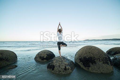 istock Young woman exercises yoga on a boulder at Moeraki boulders 522140104