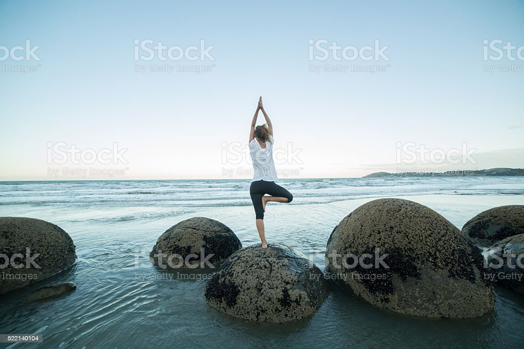 Young woman exercises yoga on a boulder at Moeraki boulders stock photo