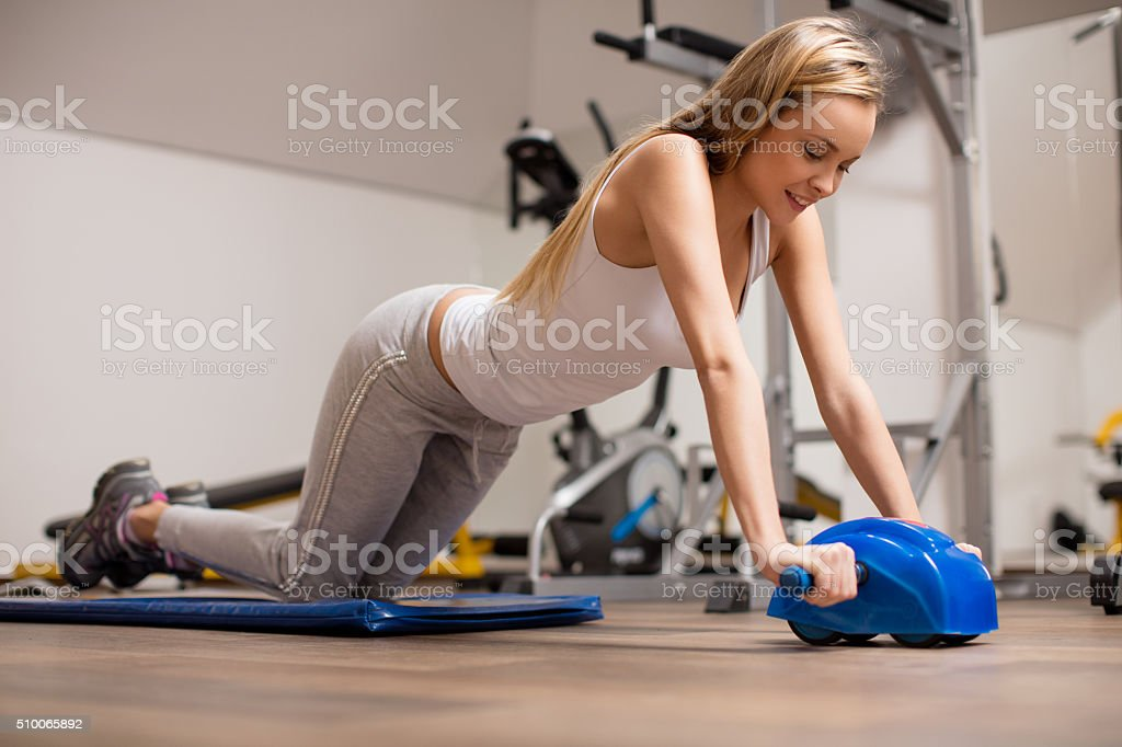 Young woman exercising abs with wheel stock photo