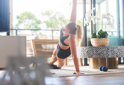 Young woman exercising at home. She is lying down doing stretching exercises with some weights. She is on the rug in the living room with a balcony in the background