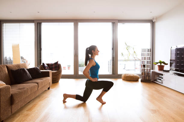 young woman exercising at home, stretching legs. - lunge stock photos and pictures