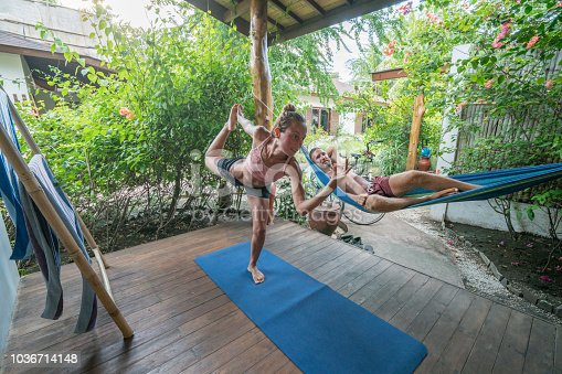 Young woman exercising at home yoga and man relaxing on hammock- People workout on vacations and zen like concept