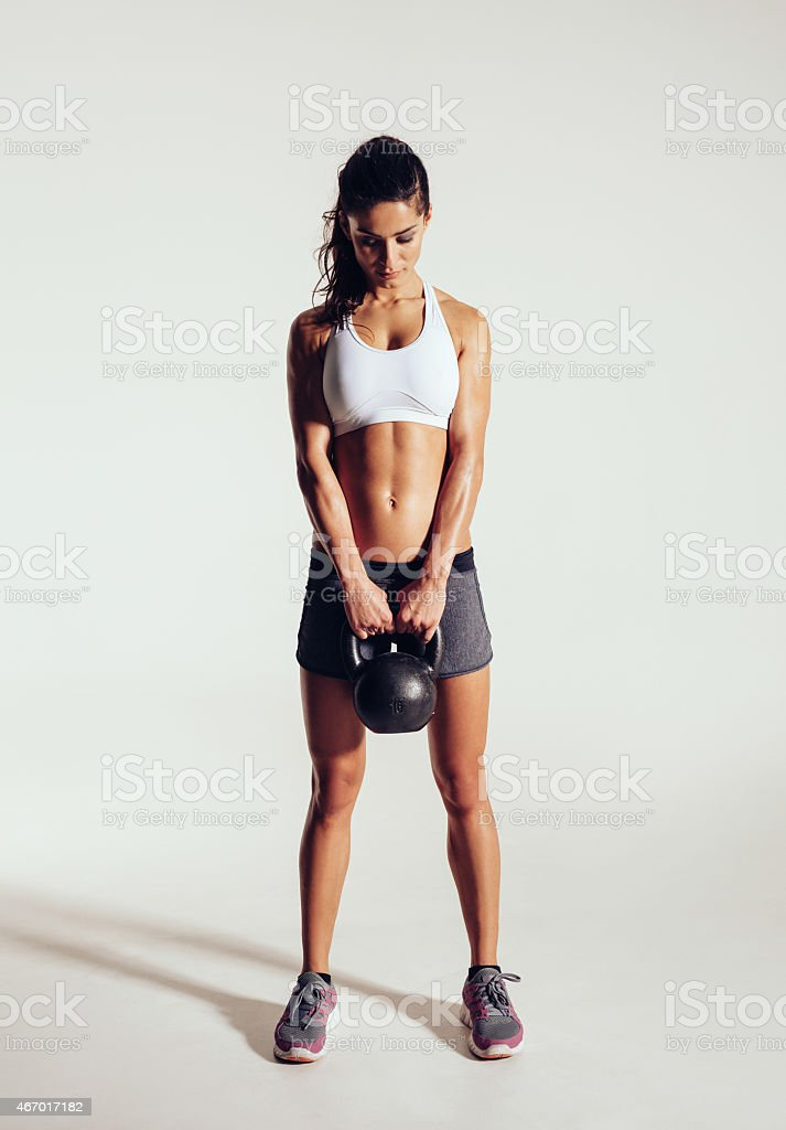Young woman exercising gym with kettle bell stock photo