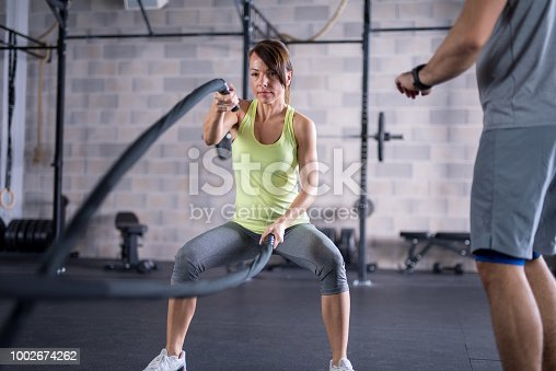 Young woman using battling ropes in gym under supervision of personal trainer.