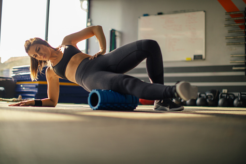 Young muscular woman using foam roller for stretching muscles after hard weightlifting training