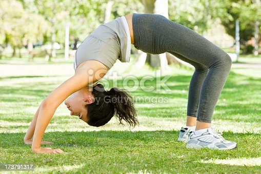 873786782istockphoto Young woman exercising in park 173791317
