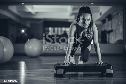 Young woman doing push-ups on exercise stepper in the gym