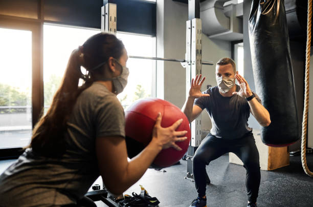 Young Woman Exercising  In The gym With Assistance From Her Personal Trainer During Coronavirus Pandemic stock photo